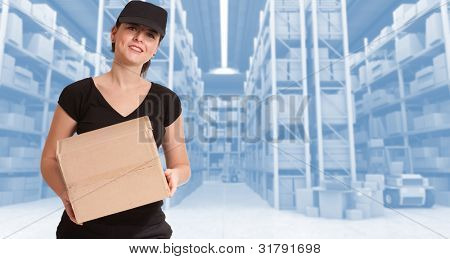 Female courier carrying a parcel in a distribution warehouse