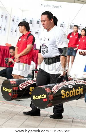 TOA PAYOH, SINGAPORE - MARCH 24 : Contender for Strongman  Keith Wong attempts the 2 times 120 log walk in the Strongman Challenge 2012 on March 24, in Toa Payoh Hub, Singapore.