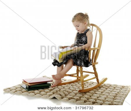 An adorable preschooler seriously enjoying books her her child-sized rocker.  On a white background.
