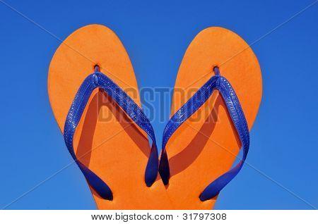 a pair of orange flip-flops over the blue sky