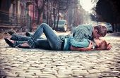 stock photo of teenage girl  - Couple of teenagers lying in street together - JPG