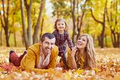 Family Lying On Yellow Leaves In The Park In Autumn. poster