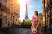 Asian Girl Walking In Small Paris Street With View On The Famous Paris Eiffel Tower On A Cloudy Rain poster
