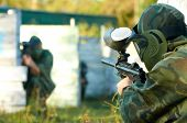 foto of paintball  - paintball sport player in protective uniform and mask aiming and shooting with gun outdoors - JPG