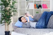 Happy young girl  relaxing on the sofa enjoying and texting  message