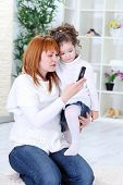 Mother and child using a mobile phone together