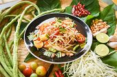 Papaya Salad Served On Wooden Dining Table / Green Papaya Salad Spicy Thai Food On Plate With Yardlo poster