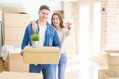 Beautiful young couple hugging in love and showing keys of new house, smiling happy moving to a new  poster