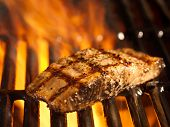 stock photo of grill  - salmon fillet on the grill with flames in horizontal orientation - JPG