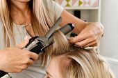 Hairstylist Using Curling Iron Of Female Client In Hairdressing Salon, Closeup View. Hairdressing Se poster