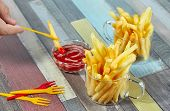 Hand Dipping French Fries On Decorative Fork In Ketchup. Hand Dipping French Fries In Ketchup. Frenc poster