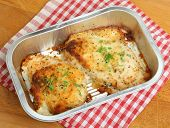 Two chicken breasts baked with cheese and herbs in convenience meal foil tray.