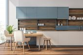 Blue And Wooden Kitchen With Counters And Table poster
