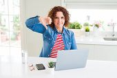 Senior woman working using computer laptop with angry face, negative sign showing dislike with thumb poster