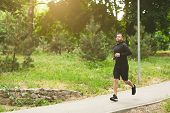 Young Sporty Man Jogging On Treadmill In Park During Morning Workout, Copy Space poster
