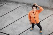 Upper View Motivated Confident Young Brunette Woman In Orange Running Jacket, Looking Up, Standing C poster