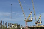 Two Construction Cranes At A Construction Site. Tall Crane On A Blue Sky. The Construction Of A Mult poster