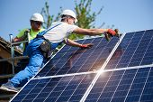 Two Workers Technicians Installing Heavy Solar Photo Voltaic Panels To High Steel Platform. Exterior poster