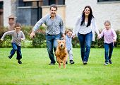 stock photo of dog-house  - Happy family running with their dog outdoors - JPG