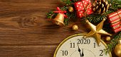 New Years 2020 Eve. Retro Style Clock With Christmas Decorations And Gifts On Brown Wooden Backgroun poster