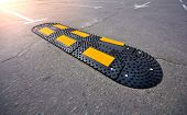 Speed Bump On Asphalt Road. Speed Limit Tool In A City. poster