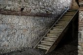 Old Wooden Stairs To The Attic In An Old House. Old Wooden Stairs In A House Built Of Stone Walls poster