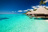 stock photo of french polynesia  - Villas on the green tropical beach with steps into water - JPG
