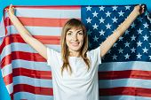 Young Woman Holds The Usa Flag On A Blue Background. Usa Visa Concept, English, Independence Day, Ju poster