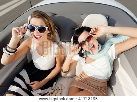 Top view of happy women with sunglasses sitting in the cabriolet