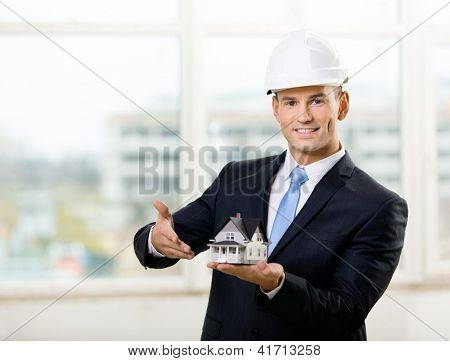 Engineer in white hard hat pointing at small model house. Concept of real estate