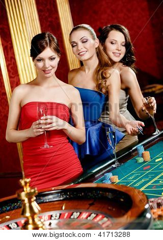 Women keeping glasses of spirits play roulette at the gambling house