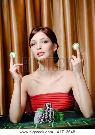 Woman with chips sitting at the playing table at the gambling house