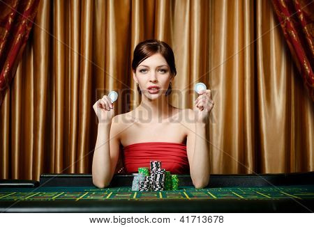Woman with chips sitting at the roulette table at the gambling house