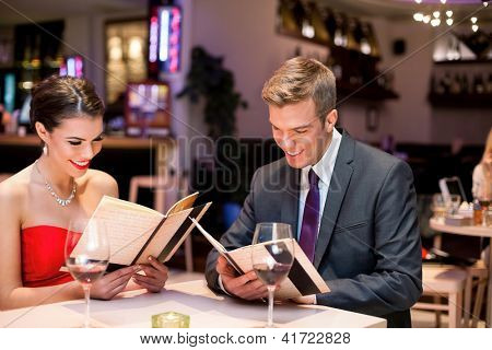 young happy couple dining out in restaurant and reading menu