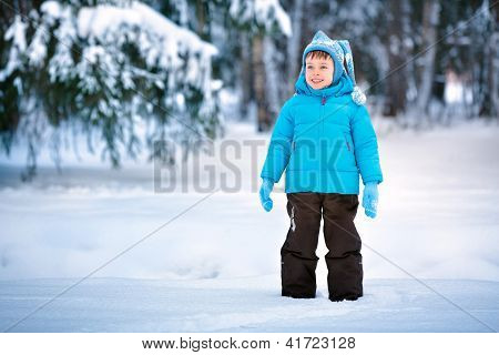 Cute little boy playing on winter forest