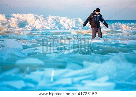 Man walking on icy beach along the Baltic sea