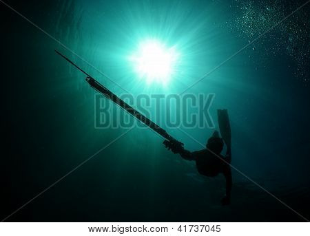 Silhouette Of Man Spearfishing