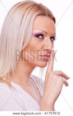 Beautiful blonde showing shush with index finger on the lips