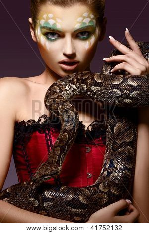 Serpent. Fantasy. Fancy Woman Holding Tamed Snake In Hands