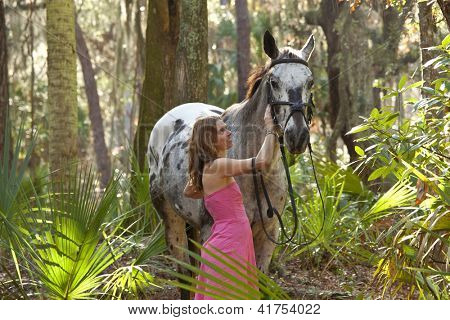 woman in pink dress with horse in forest