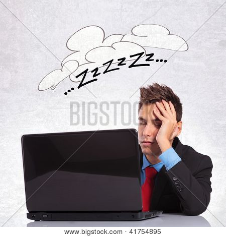 young business man sleeping on his office desk with laptop