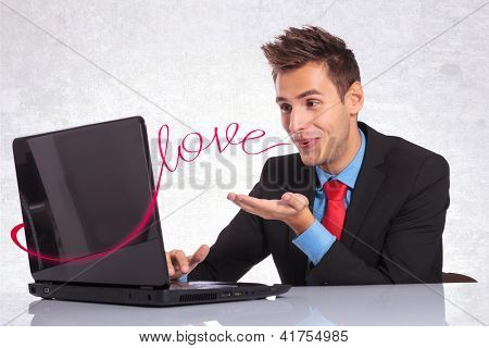 young man in suit sending his love to the person to whom is on a computer chat with