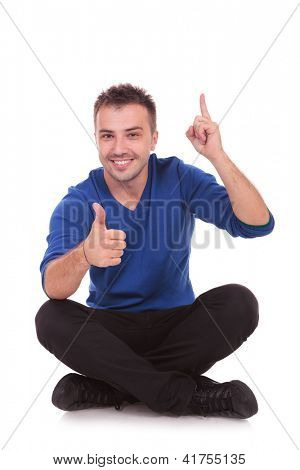 Portrait of a casual young man sitting on the floor, legs crossed, giving the thumbs up and pointing upwards, all this with a big smile on his face.