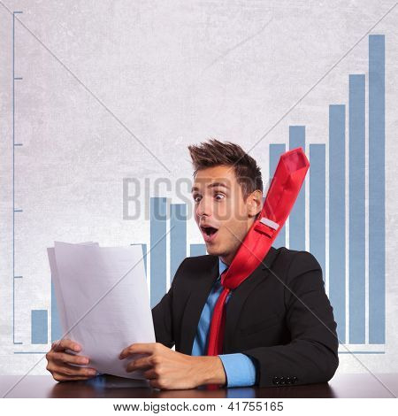 very excited business man with flying tie reading the good news on his documents