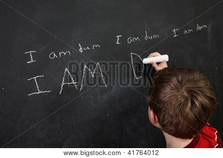 Boy with poor spelling and low self esteem writing on a blackboard