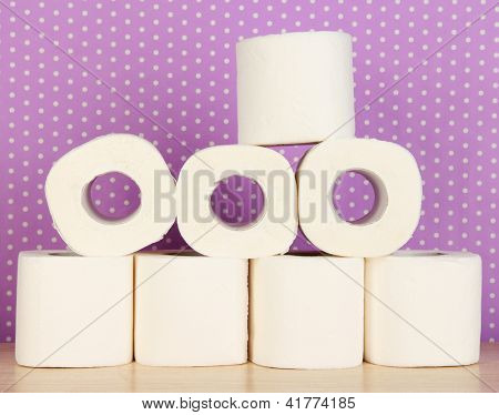 Rolls of toilet paper on purple with dots background
