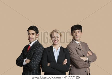 Portrait of young multi ethnic team with arms crossed over colored background