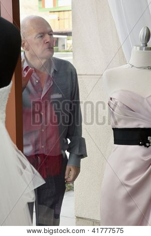 Senior man looking at wedding dress displayed on window in bridal store