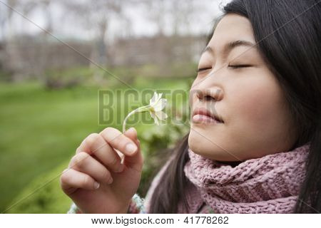 Close-up of a young Asian woman smelling flower in park