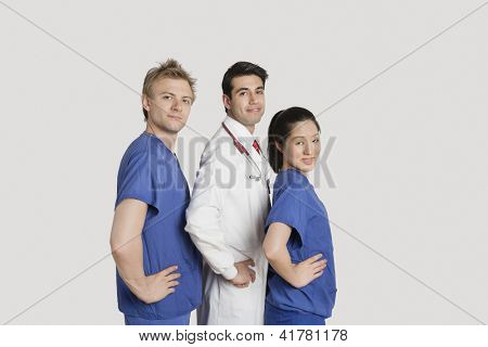 Portrait of medical team standing hands on hips over gray background